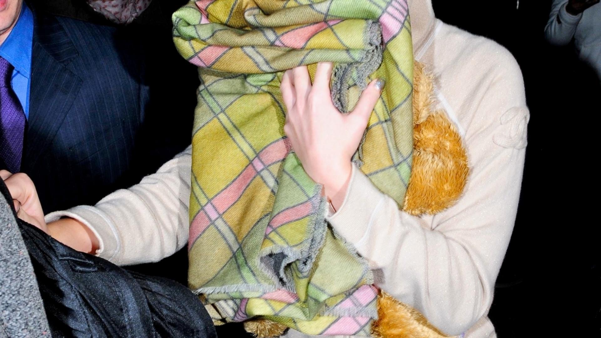 Katy Perry se esconde dos fotógrafos com um cobertor em sua chegada no aeroporto de Los Angeles, EUA (25/3/2012)