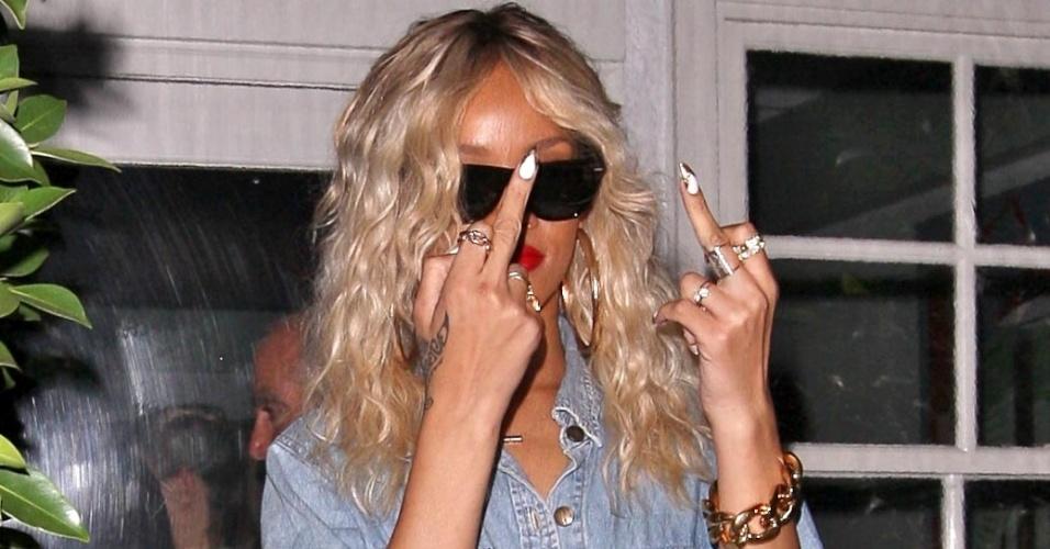 Irritada com a presença de fotógrafos,Rihanna mostrou os dedos médios, em sinal de insulto, enquanto jantava no restaurante Giorgio Baldi em Santa Mônica, na Califórnia (EUA) (23/3/12)