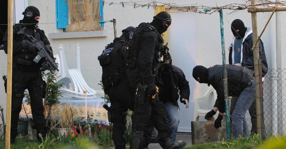 Agentes de forças especiais de segurança francesas inspecionam jardim de casa de um dos suspeitos de envolvimento com grupos islamistas presos em Coueron