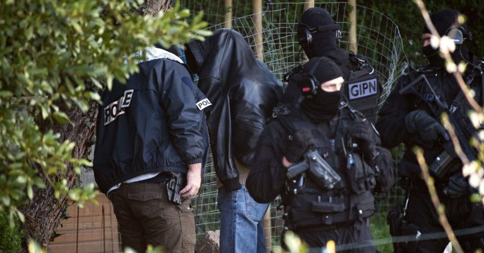 Em uma operação que resultou na detenção de 20 pessoas ligadas a grupos islamitas na França, policiais prendem um homem em Coueron, no oeste da França, nesta sexta-feira (30), dias depois que o massacre de Toulouse abalou o país