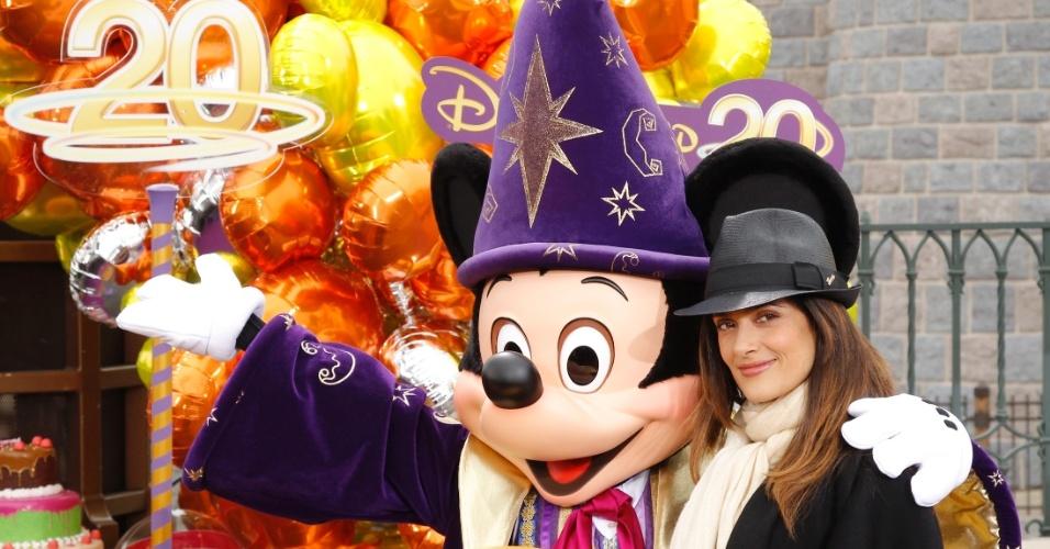 A atriz Salma Hayek posa para fotos com o Mickey durante a comemoração de 20 anos do resort da Disney em Marne-la-Vallee, cidade próxima à Paris (31/3/12)