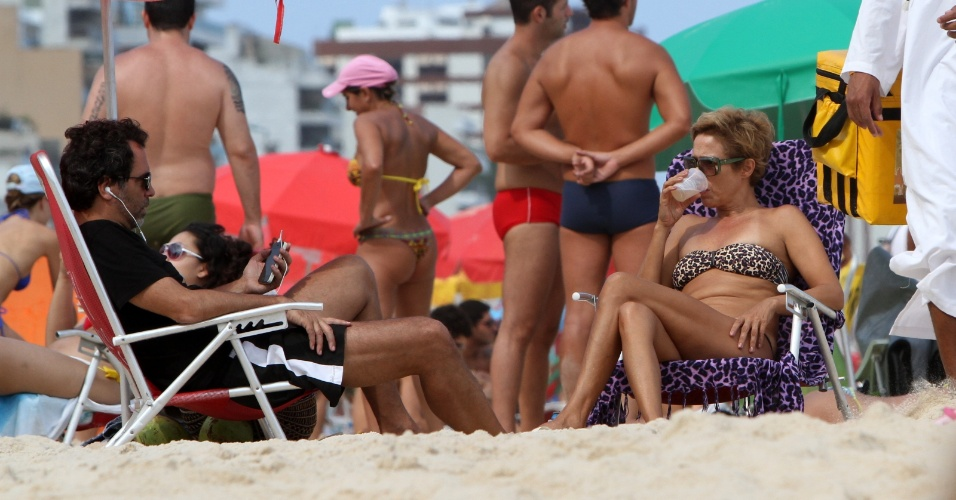 Andréa Beltrão aproveita o domingo de sol e curte a praia com o marido. A atriz lê jornal e bebe cerveja na praia de Ipanema, no Rio de Janeiro (1/4/12)