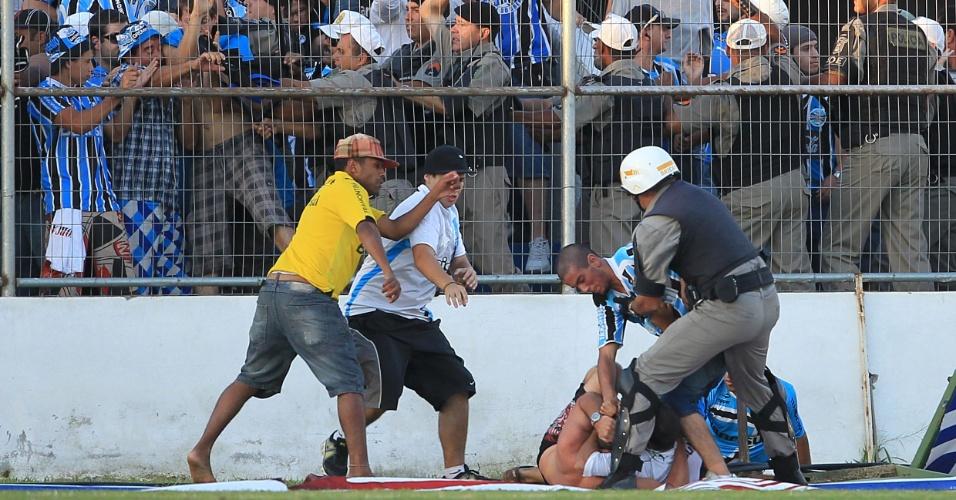 Policial se esforça para interromper briga entre torcedores na partida Grêmio x Pelotas