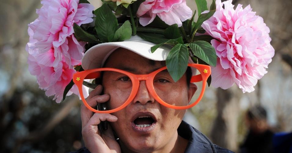 Vendedor ambulante usa chapéu com flores em Pequim, na China, no início da época de flores de cerejeiras