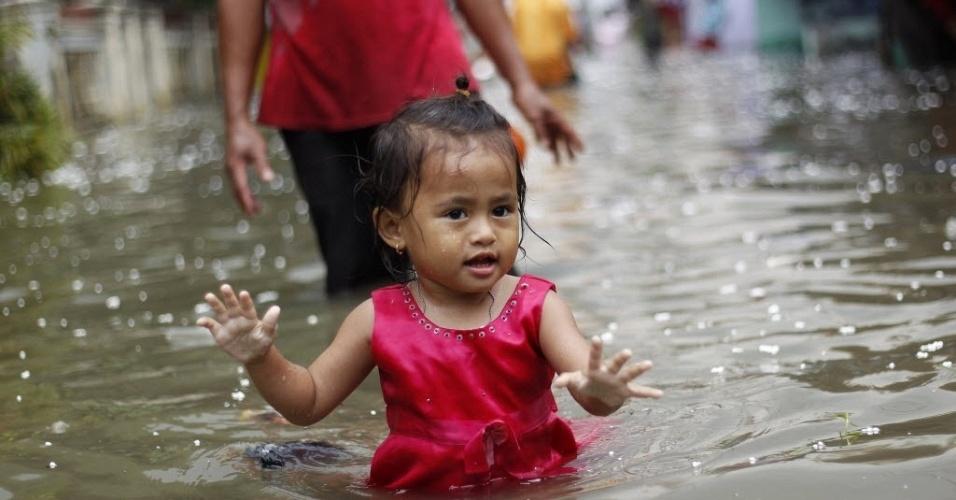 Criança brinca em área residencial alagada em Jacarta, capital da Indonésia inundada pelas fortes chuvas de segunda (2) e terça-feira