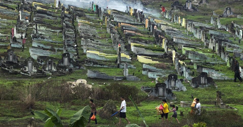 Famílias visitam tumbas de parentes durante o Dia dos Mortos, em Kuala Lumpur, na Malásia
