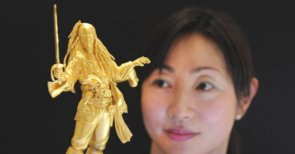 Funcionária de loja de departamentos de Tóquio (Japão) exibe estátua de ouro do pirata Jack Sparrow, personagem do filme Piratas do Caribe. A loja lançou a estátua, de 26cm de altura e 1,8 kg de ouro puro, em homenagem ao 110º aniversário do nascimento do diretor de cinema Walt Disney. O item está à venda por US$ 435 mil