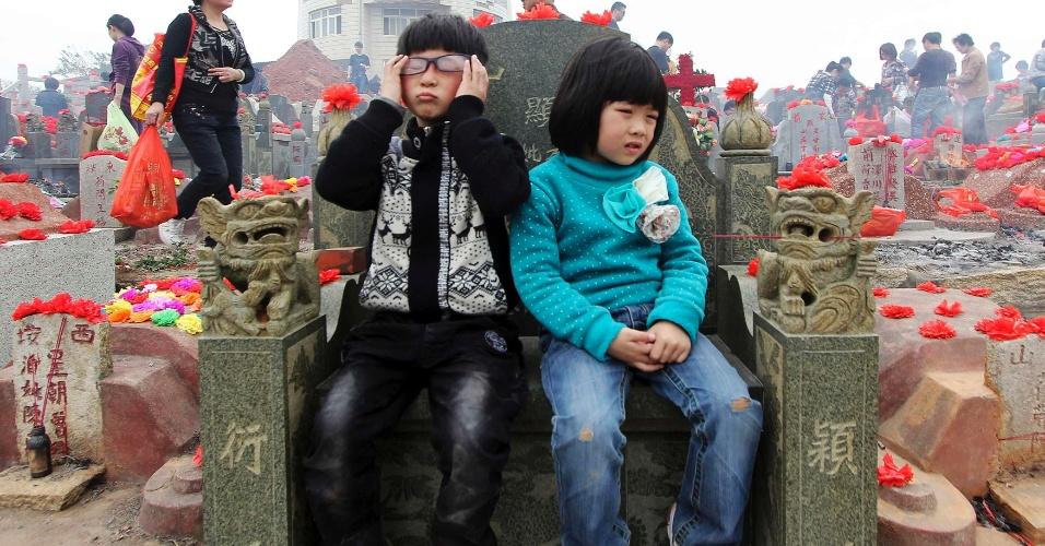 Crianças esperam familiares sentadas em frente a tumba em cemitério público em Jinjiang, na China, durante o festival Qingming