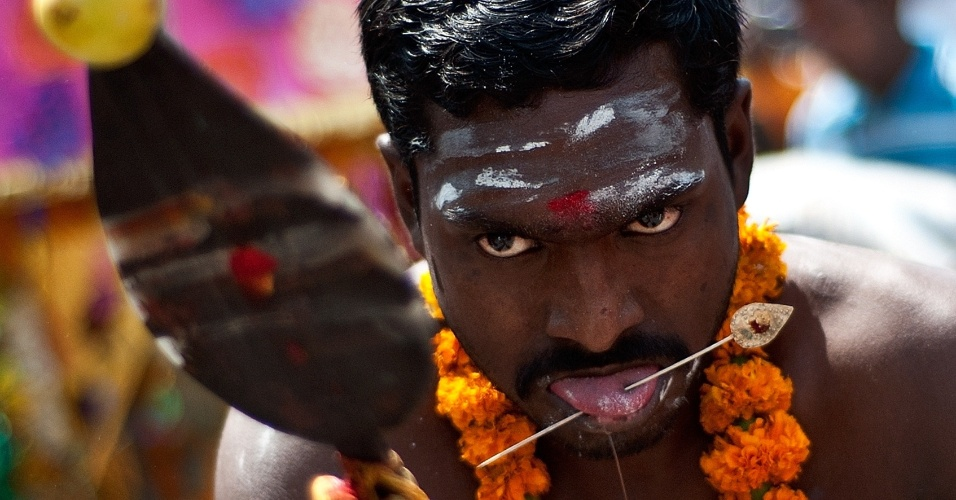 Indiano usa ferro atravessado na língua durante procissão religiosa em Nova Déli, na Índia, nesta quinta-feira (5). Ele puxa uma carruagem em homenagem a Murugan, conhecido como filho de Shiva. Neste tipo de procissão, os indianos costumam carregar potes de leite sobre as cabeças e perfurar partes do corpo com peças de ferro