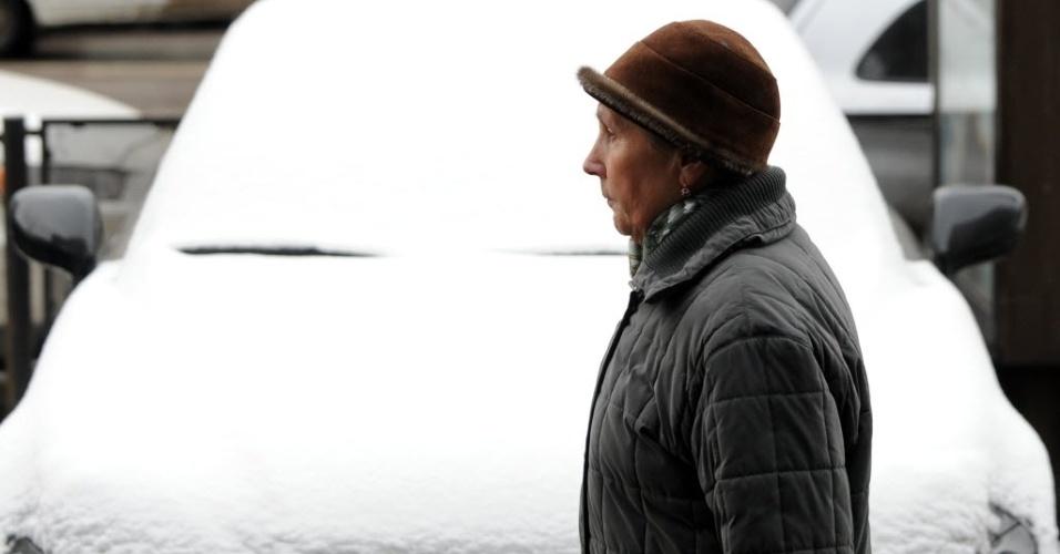 Mulher passa em frente a carro coberto de neve no centro de Moscou, na Rússia, nesta quinta-feira (5). Os moradores da capital russa acordaram com a cidade coberta de neve após a passagem de um forte ciclone, que levou a Moscou uma tempestade de inverno no meio da primavera