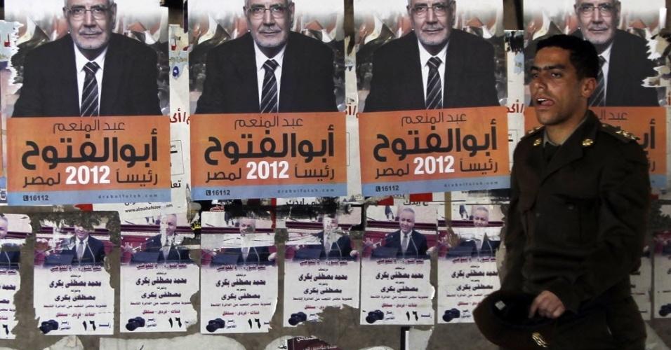 Oficial do exército passa em frente a cartazes do candidato à presidência do Egito, o ex-líder da Irmandade Muçulmana, Abdel Moneim Abol Fotoh, no Cairo, capital egípcia. As eleições presidenciais serão disputadas em 23 e 24 de maio