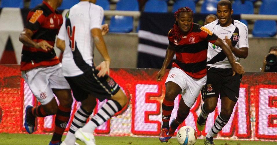 O atacante rubro-negro Vágner Love carrega a bola e tenta passar pela marcação no clássico entre Flamengo e Vasco, no estádio do Engenhão