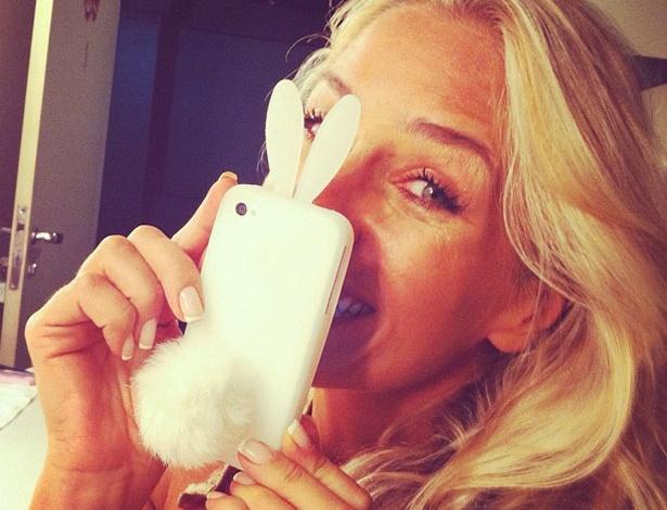 """Adriane Galisteu postou uma foto em seu perfil do Twitter com uma capinha de celular de coelho. A apresentadora disse que o presente foi uma piada da amiga, a atriz Lúcia Veríssimo: """"@luciaverissimo: Hj chegou dizendo que quer me irritar e trouxe 1 com pompom. Mais tarde foto d'eu estrangulando ela kkkk"""" (8/4/12)"""