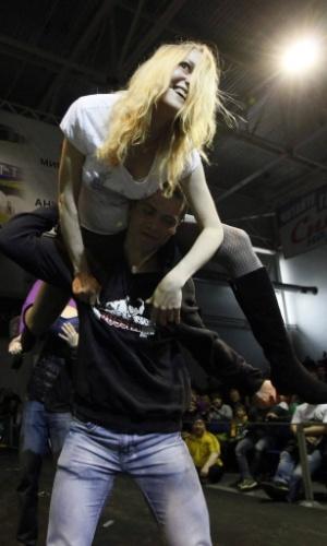 Espectadora é carregada durante campeonato de força extrema realizado na cidade russa de Krasnoyarsk, na Sibéria