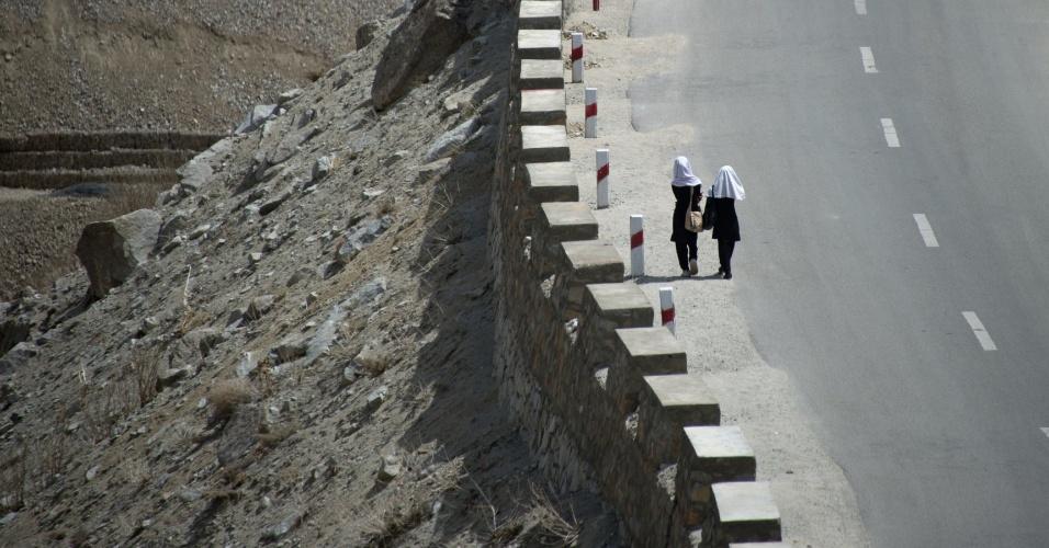 Mulheres afegãs caminham ao longo de uma estrada perto de Saricha Hill, em Bazarak, vila no vale de Panjshir, no norte do Afeganistão