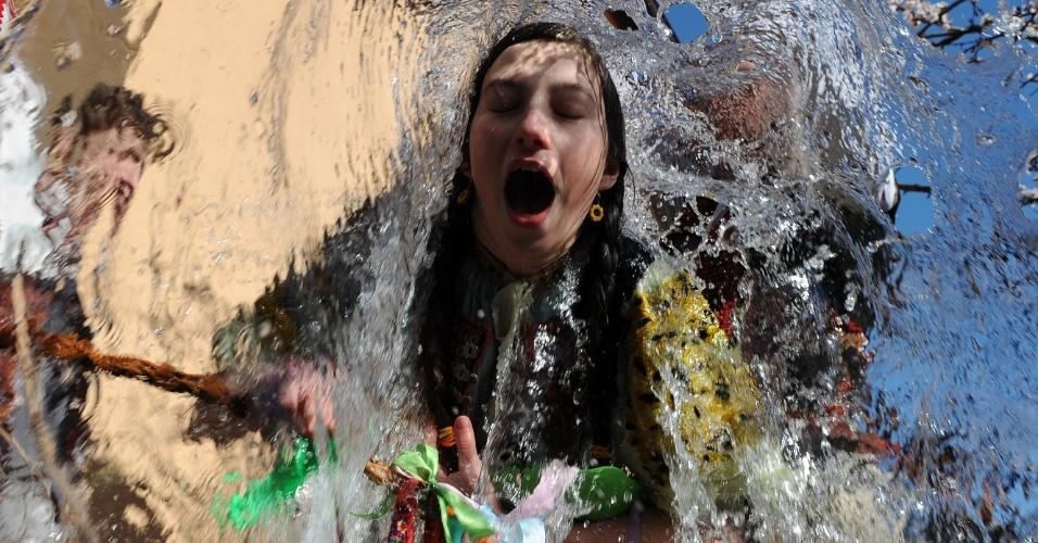 Garota toma banho de balde de água nesta durante celebrações da Páscoa no vilarejo Trencianska Tepla, na Eslováquia