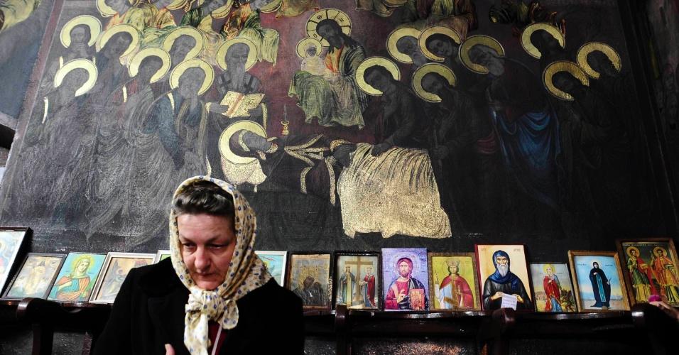 Mulher na igreja St. Dimitrie em Skopje, onde de acordo com um padre, pinturas de símbolos sagrados começaram a brilhar por conta própria, na Macedônia