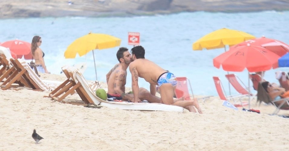 O estilista americano Marc Jacobs (esq) troca beijos com o namorado, o ator pornô brasileiro Harry Louis (dir), na praia da Ipanema, zona sul do Rio (9/4/2012)