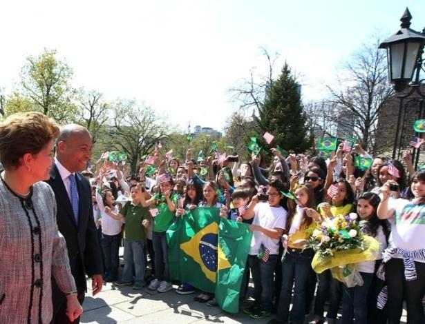 Dilma Rousseff observa crianças com bandeiras do Brasil e Estados Unidos ao lado do governador de Massachusetts, Deval Patrick, em Boston