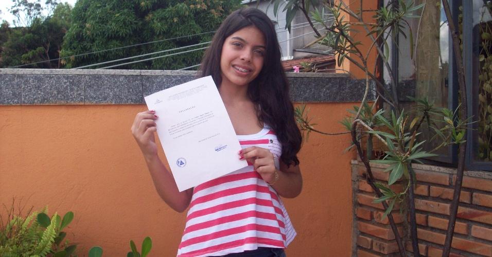 Lorena Aguiar Ribeiro,13, posa com comprovante de aprovação no curso de direito de uma faculdade particular em Belo Horizonte