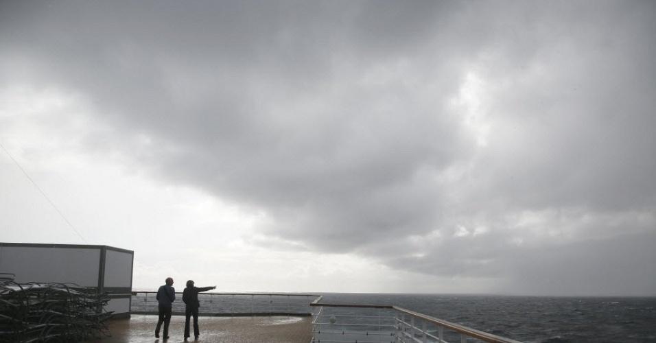 Passageiros observam as nuvens no convés do cruzeiro Titanic Memorial Cruise, que reproduz a expedição da embarcação Titanic, que naufragou em 1912. O cruzeiro mudou seu rumo em direção à Irlanda por um problema médico a bordo, um passageiro com um problema cardíaco de baixa gravidade