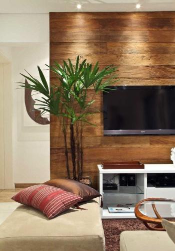 O painel de madeira de demolição em tábuas, da Assoalhos Monet, é fixado à alvenaria sobre barrotes verticais e