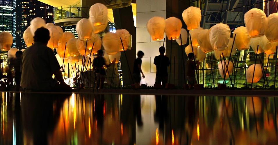 Voluntários fixam luminárias no Marina Bay Sands Artscience Museum, em Cingapura, em memória ao naufrágio do Titanic