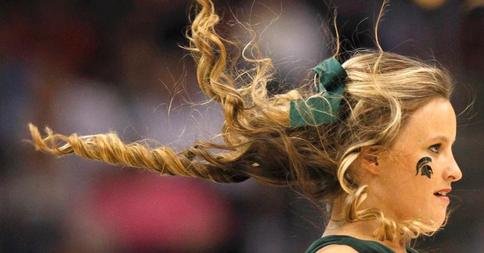 Cabeleira loira de cheerleader balança no ar durante exibição em jogo de basquete dos EUA