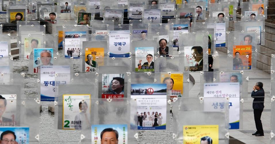 Homem olha para cartazes eleitorais instalados em para impulsionar os votos em Seu
