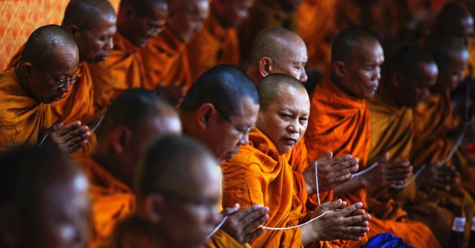 """Monges budistas se juntam a familiares e amigos dos membros mortos do movimento """"camisa vermelha"""" durante oração em Bangcoque"""