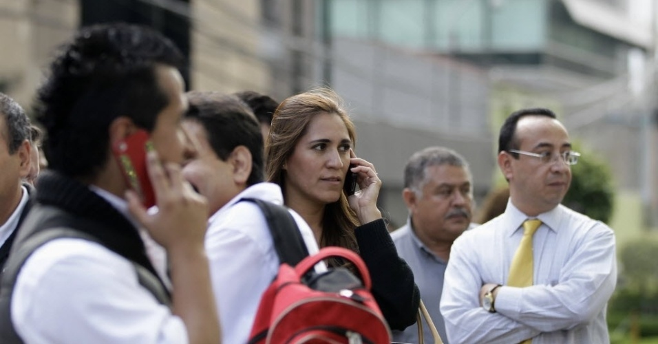Mexicanos falam ao celular ap&#243;s evacua&#231;&#227;o de pr&#233;dio devido a tremor de terra que abalou a Cidade do M&#233;xico. Segundo  Servi&#231;o Geol&#243;gico dos Estados Unidos (USGS, na sigla em ingl&#234;s), o tremor teve magnitude 7,0