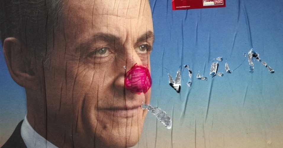 Cartaz vandalizado mostra o candidato à reeleição para presidente da França, Nicolas Sarkozy