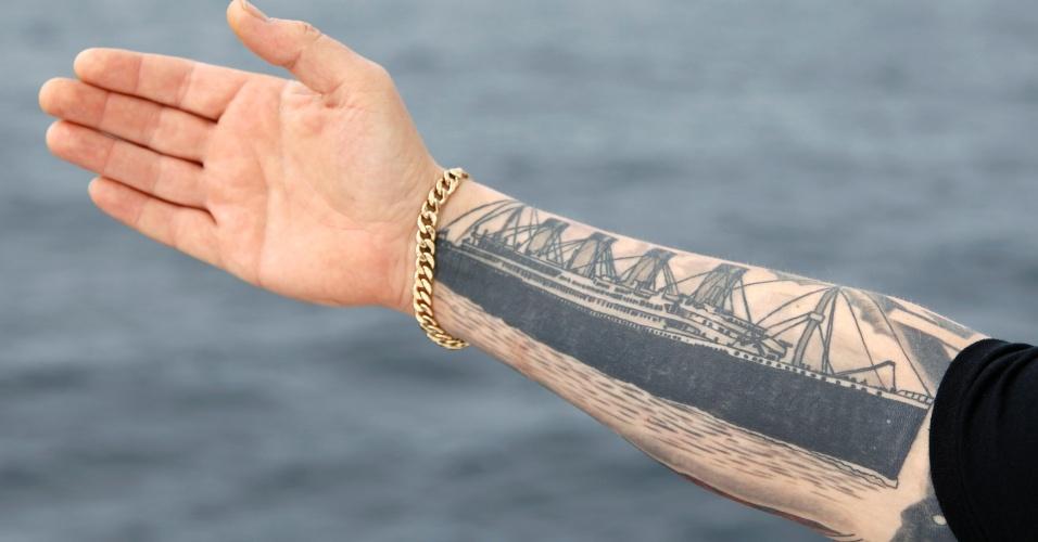 Derek Chambers, de Belfast, exibe uma tatuagem do Titanic a bordo do cruzeiro em homenagem ao navio, nesta quinta-feira (12), no oceano Atlântico.