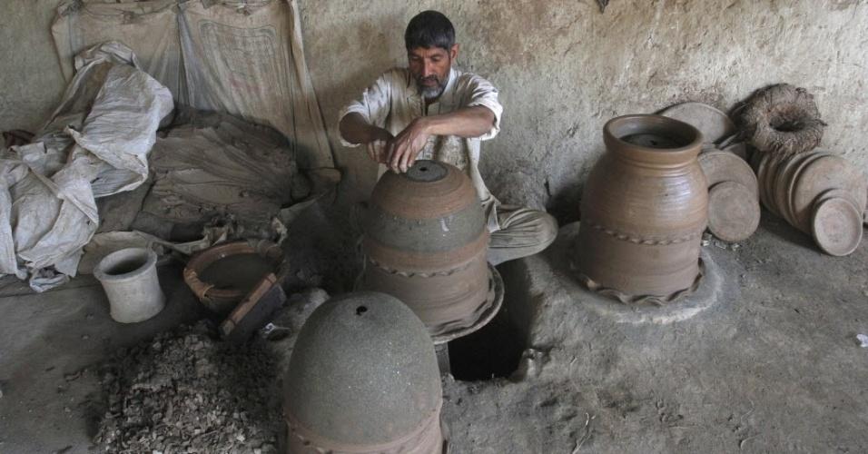 Homem esculpe pote de cerâmica nos subúrbios de Peshawar, no Paquistão