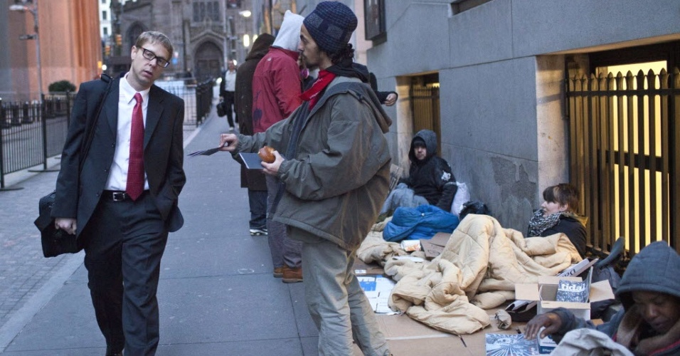 Integrantes do movimento Occupy Wall Street distribui panfletos em acampamento rec&#233;m-montado na cal&#231;ada pr&#243;xima &#224; bolsa de Nova York (ao fundo, &#224; direita), nesta quinta-feira (12) 