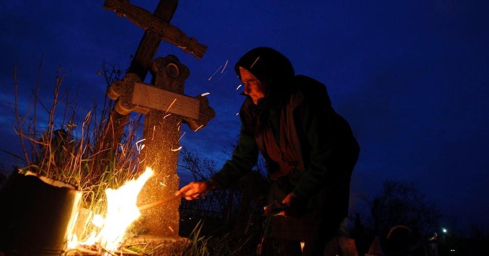 Mulher acende uma fogueira em frente aos túmulos de seus parentes em um cemitério na vila de Copaciu, em Bucareste