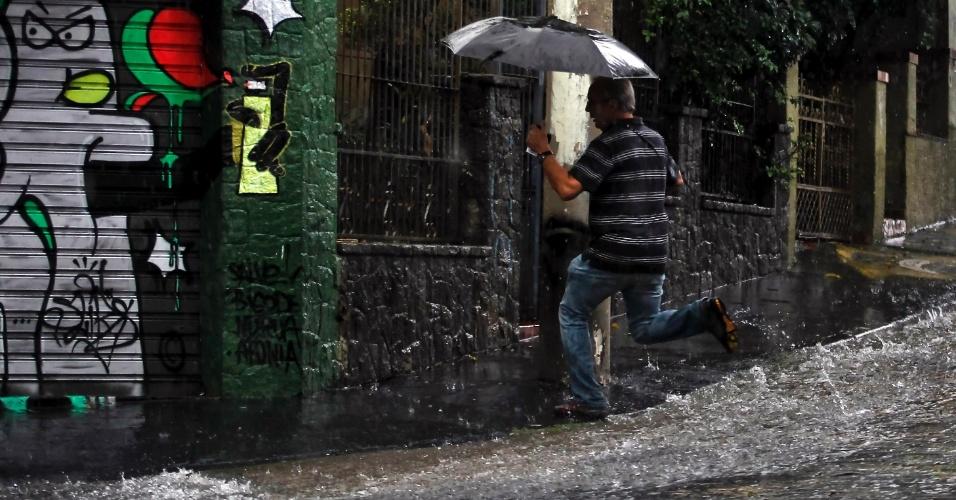 Pedestre enfrenta rua alagada na vila Madalena, zona oeste de São Paulo, durante a forte chuva que atingiu a capital paulista nesta quinta-feira (12) e chegou a deixar todas as regiões em estado de atenção a alagamentos.