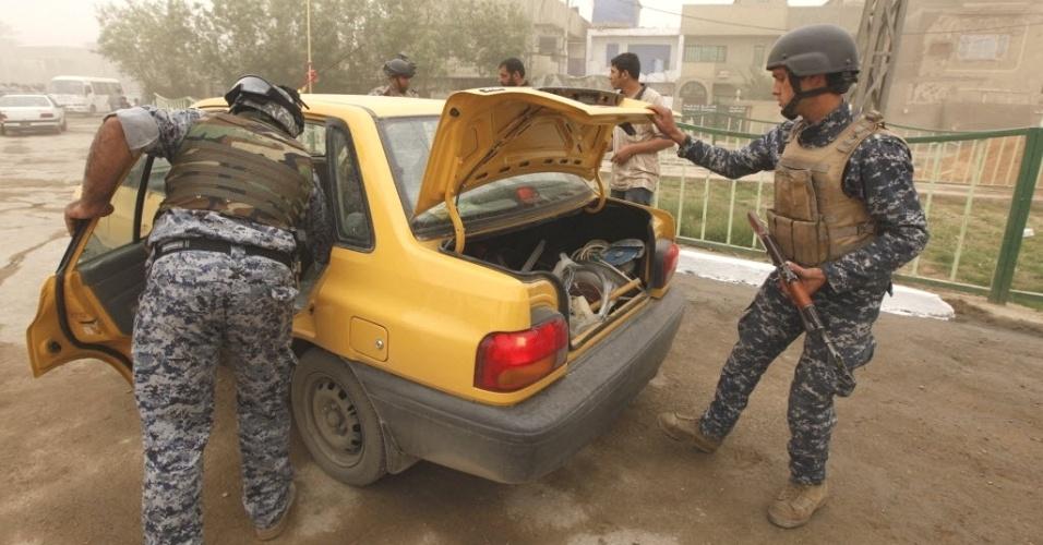 Policiais iraquianos revistam veículo após reabertura de uma das vias principais do distrito de Saidiya, na capital do país, Bagdá