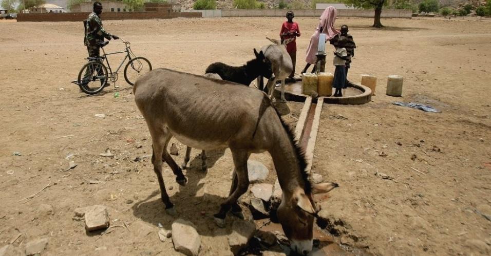 Soldado sudanês passa por família bombeando água do mesmo local onde bebem animais, próximo à cidade de Talodi, na fronteira do Sudão com o Sudão do Sul