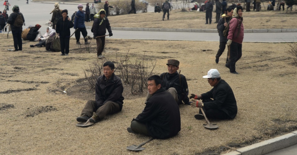 Trabalhadores fazem intervalo em rua de Pyongyang, na Coreia do Norte