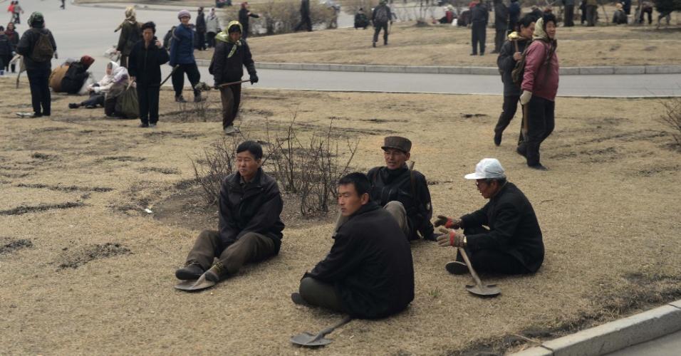 Trabalhadores fazem intervalo em rua de Pyongyang, na Coreia do Norte