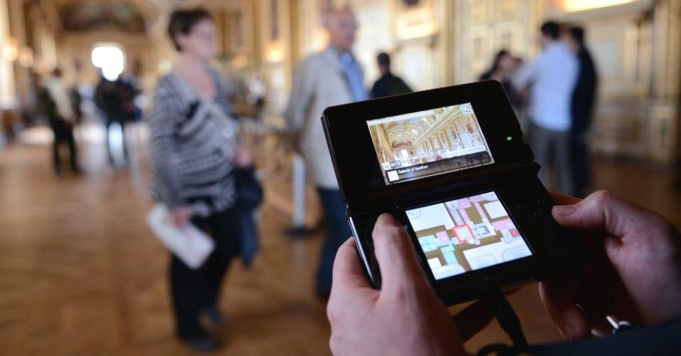 Visitante usa videogame portátil adaptado para substituir guias, em passeio pelo museu do Louvre, em Paris (França)