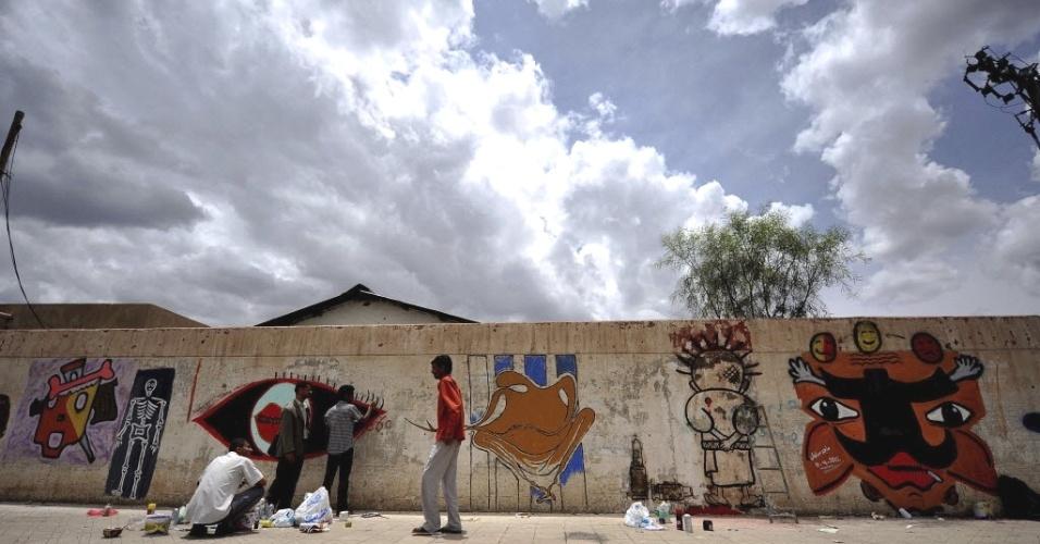 Voluntários iemenitas pintam muro de casa que sofreu danos durante as revoltas contra o governo do presidente Ali Abdullah Saleh, em Sanaa, capital do país