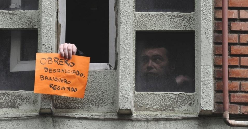 """Ativista antidespejo segura cartaz onde se lê """"trabalhador desabrigado, banqueiro resgatado"""" em janela de prédio habitado irregularmente por família equatoriana em Oviedo (Espanha)"""