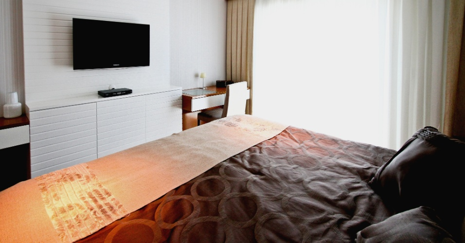 Em frente à cama do casal, no apartamento no Jardim França, em São Paulo, o móvel sustenta a TV e se prolonga como mesas laterais de apoio. O projeto da decoração é assinado por Silvia Bitelli