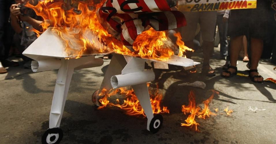 Manifestantes filipinos queimam réplica de aeronave norte-americana durante protesto em frente a embaixada dos EUA em Manila, nas Filipinas, contra manobras militares conjuntas entre os dois países