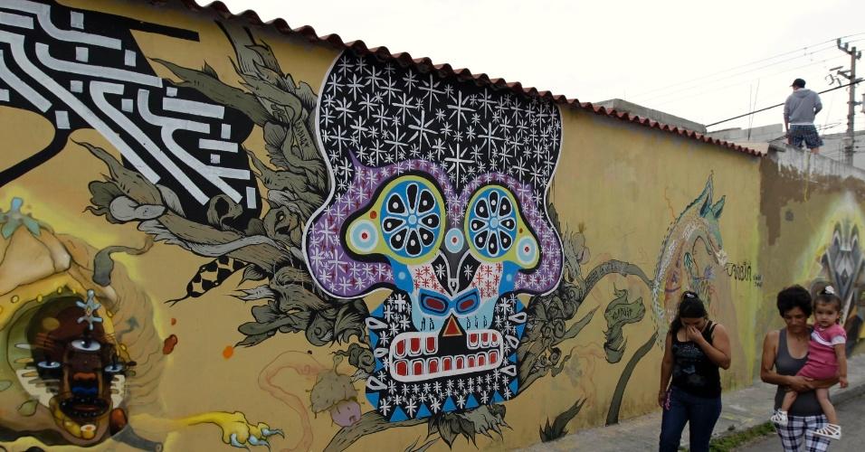 Mexicanos caminham em frente a grafite em muro de San Pedro Cholula, no México