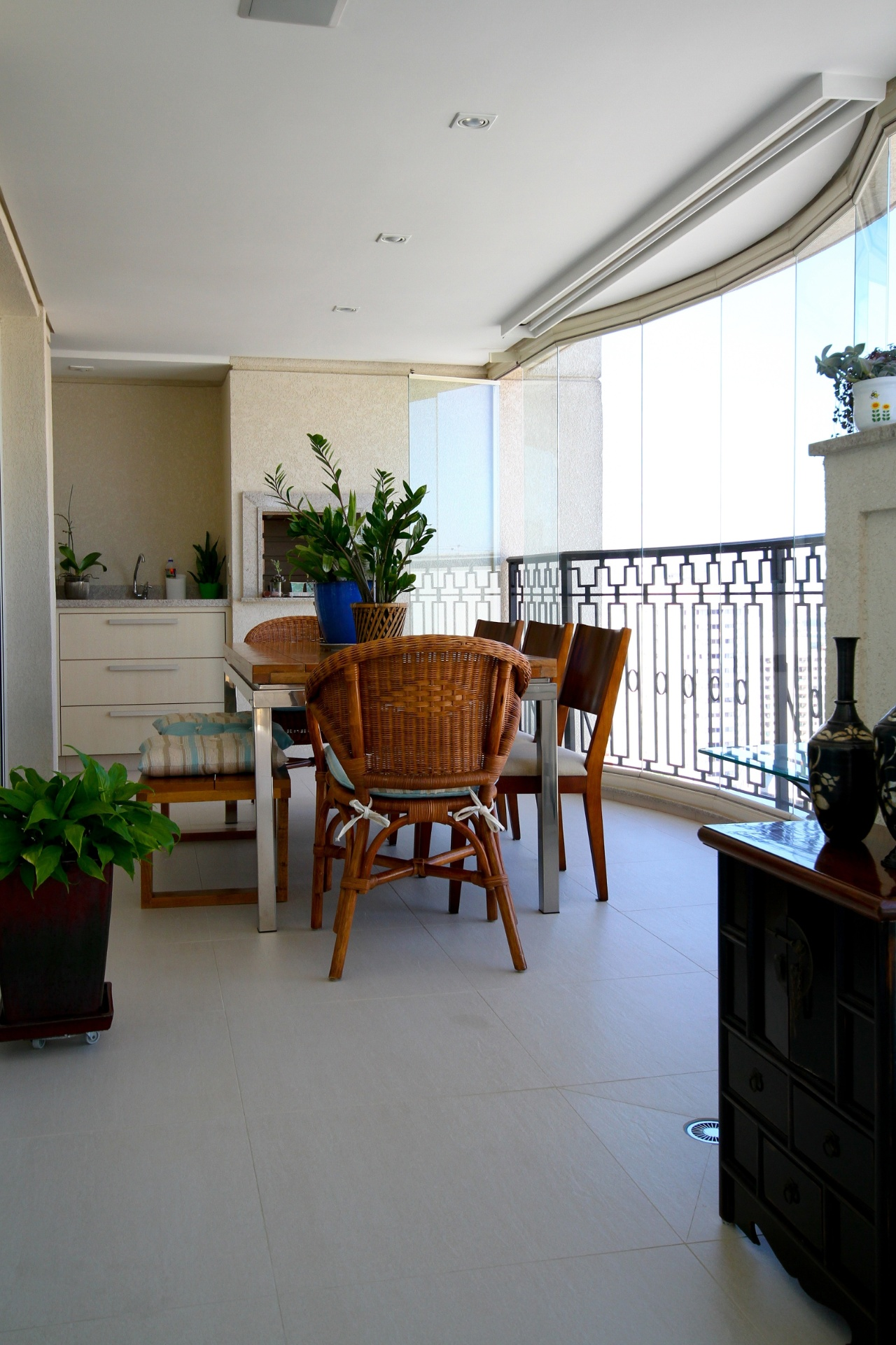 No braço da varanda, a área da churrasqueira foi mobiliada por mesa com tampo de madeira e três estilos de assento. O projeto de decoração do apartamento no Jardim França, em São Paulo, é da arquiteta e designer Silvia Bitelli