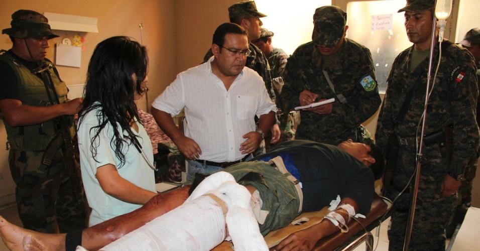 O ministro da Defesa do Peru, Alberto Otarola (centro), visita soldado ferido após ataque contra um helicóptero que participava da busca de 43 pessoas que foram sequestradas na na região de Cuzco