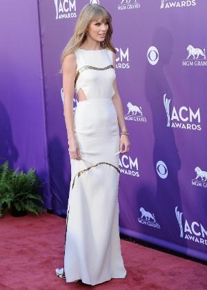 Taylor Swift usou um vestido branco da marcar J. Mendel, com recorte triangular discreto na lateral da cintura, para ir ao Academy Country Music Awards. O look da cantora foi considerado um dos melhores da noite